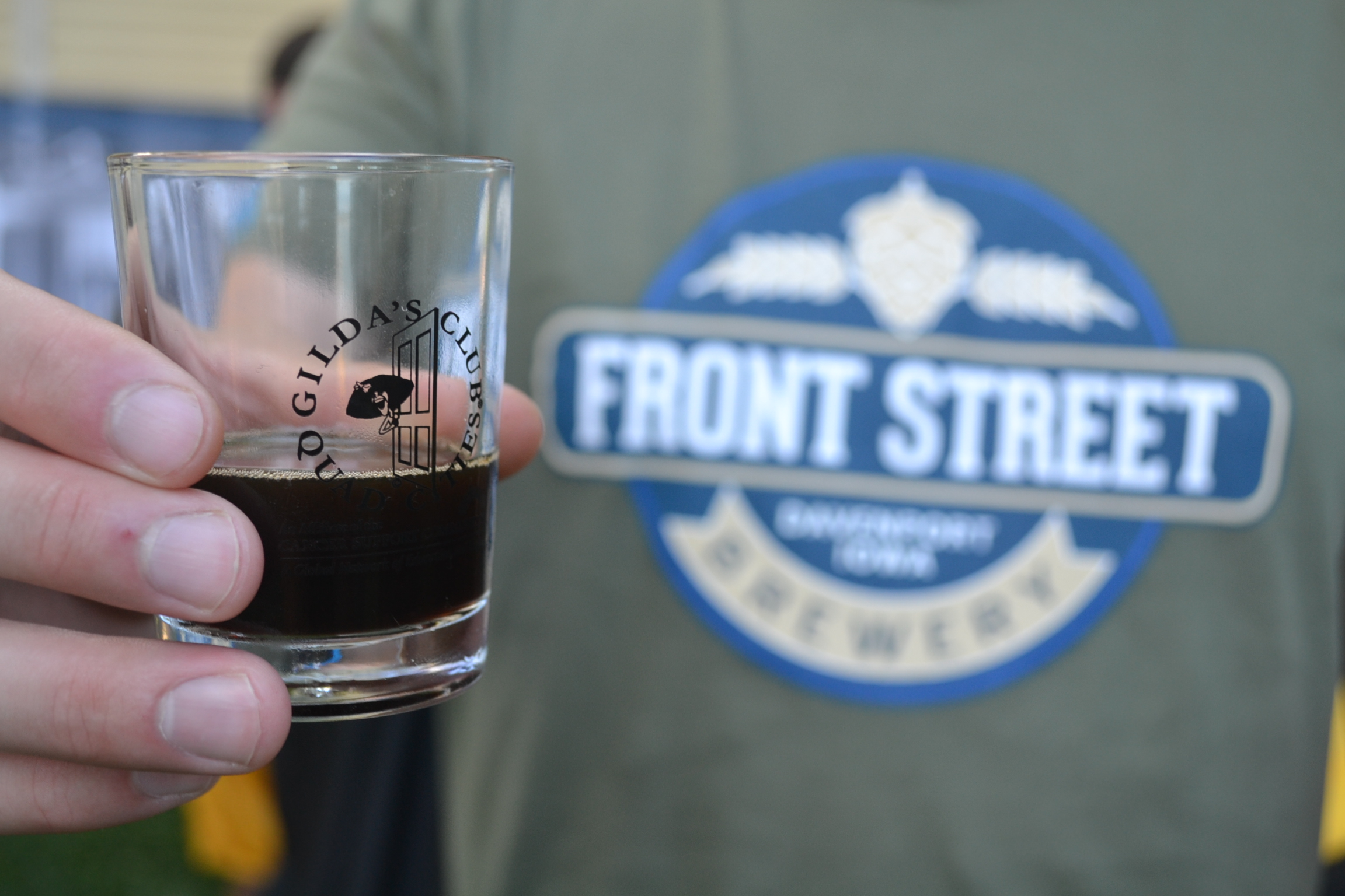 Person holding Gilda's Club tasting glass wearing Front Street shirt