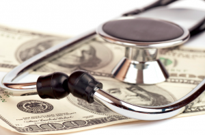Stock photo of a stethoscope lying on top of $100 bills